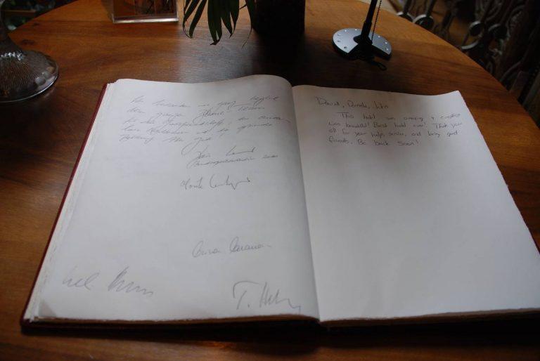 Der Bundesrat trägt sich ein im Gästebuch des Hotels Blume.